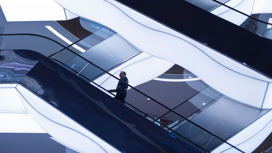 Low Angle View Of Man On Escalator In Building