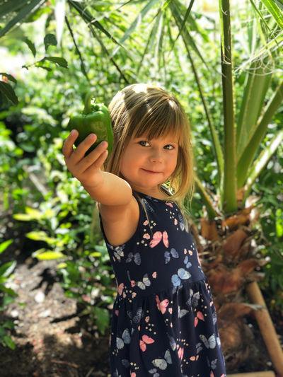 Portrait of girl holding green bell pepper against plants