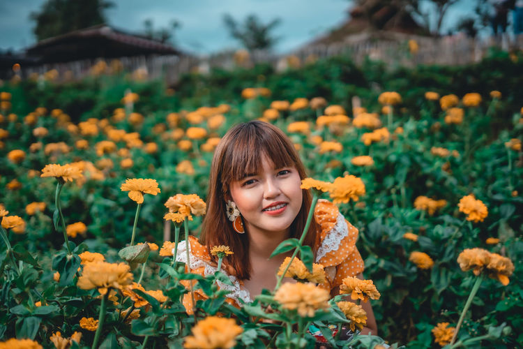Portrait of smiling woman with yellow flowering plants