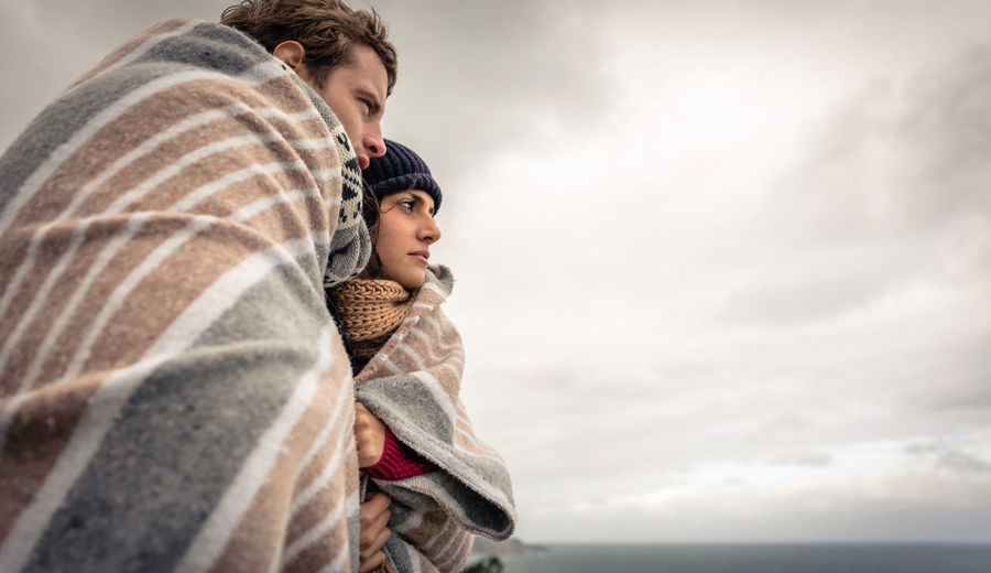 Couple covered with blanket standing against sky