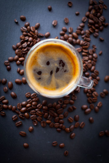 Coffee cup with fresh brewed coffee and brown roasted coffee beans scattered on black stone background top flat lay view Food And Drink Coffee Coffee - Drink Drink Refreshment Cup Mug Coffee Cup Freshness Roasted Coffee Bean Close-up No People Food Still Life Indoors  Directly Above Studio Shot Brown Seed High Angle View Caffeine Latte Non-alcoholic Beverage