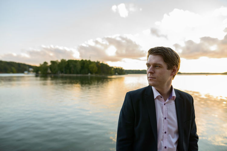 Portrait of young man standing by lake against sky