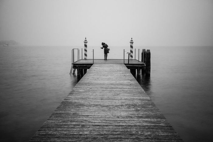 B&W jetty on a lake Blackandwhite Horizon Over Water Italia Italy Jetty Jetty Area Jetty View Lake Lake View Lakescape Lakeside Landscape Longexposure One Person Pier Rear View Silence Water