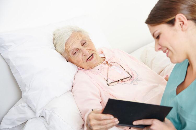 Senior woman and nurse on bed