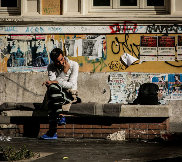 Woman with graffiti on wall in city