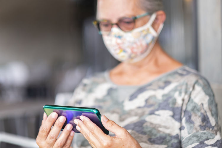 Midsection of senior woman wearing mask using smart phone at home