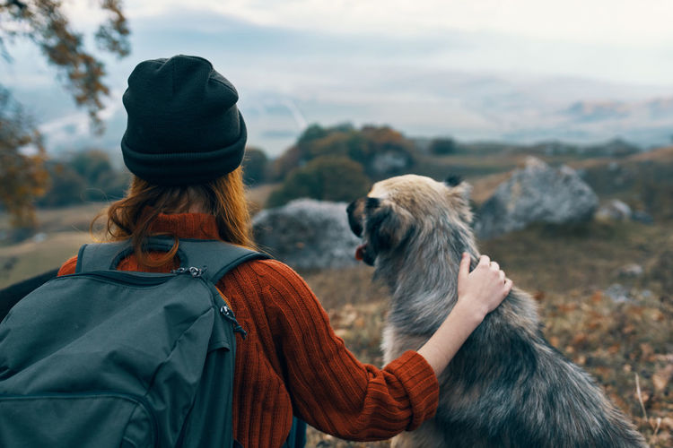 Rear view of woman with dog looking at winter