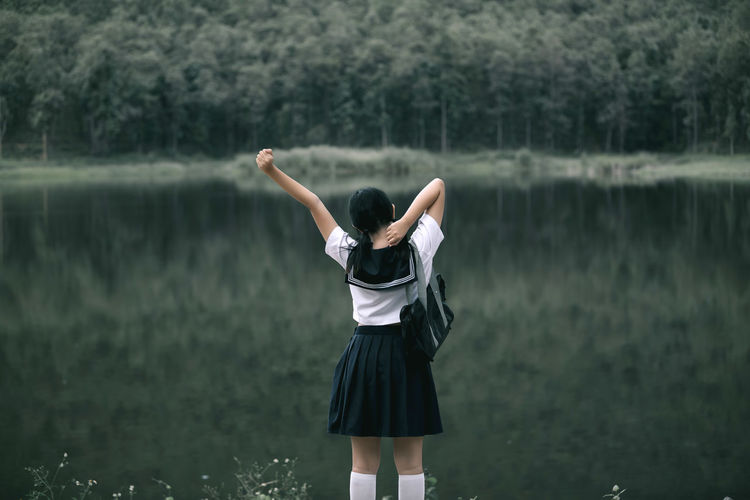 Rear view of woman wearing school uniform while standing against lake