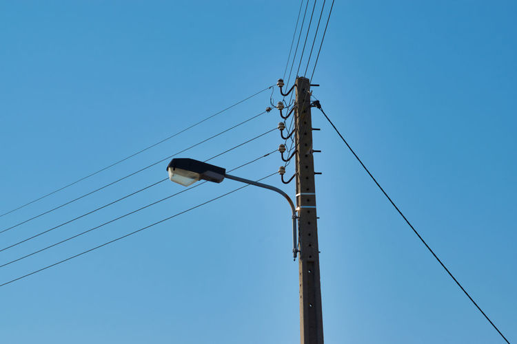 Electric wire poles Cable Connection Blue Sky Low Angle View Electricity  Power Supply Technology No People Day Nature Telephone Line Outdoors Clear Sky Electrical Equipment Power Line  Fuel And Power Generation Lighting Equipment Electricity Pylon Light Copy Space Street Light