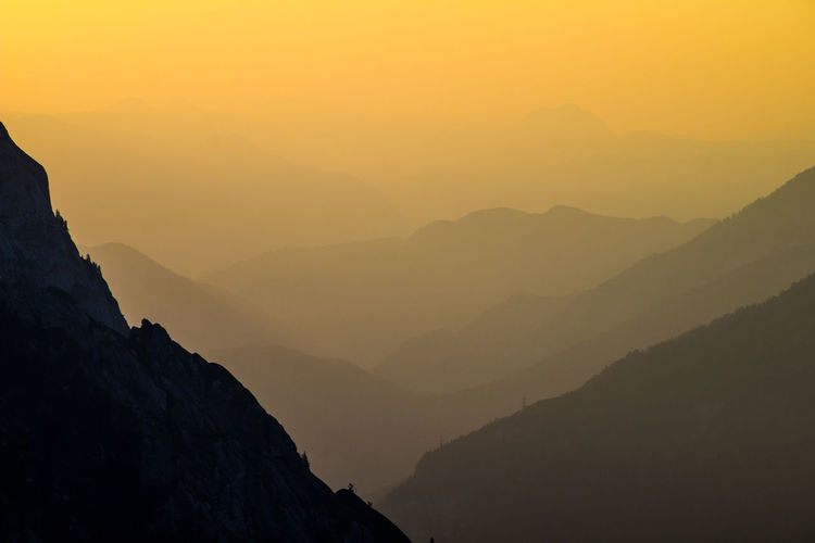 Scenic view of mountain range in foggy weather during sunset