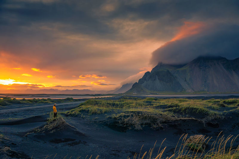 Scenic view of landscape against dramatic sky during sunset