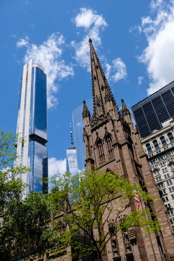 Trinity Church in New York City New York Manhattan Financial District  Wall Street  Metropolis Iconic City White Clouds And Blue Sky Urban Cityscape Streetphotography New York City NYC NY United States Of America City Architecture East Coast North America Building Skyscraper Skyscrapers Tall - High Tall Buildings Sky Built Structure Building Exterior Day Cloud - Sky Nature Outdoors Buildings High Rise High Rise Buildings Architectural Column Low Angle View Trinity Church Church Trees Old Buildings Religion Belief Place Of Worship Spirituality Plant Tree Tower No People Office Building Exterior Spire  Gothic Style