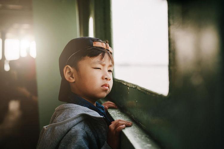 Boy looking away through window in train