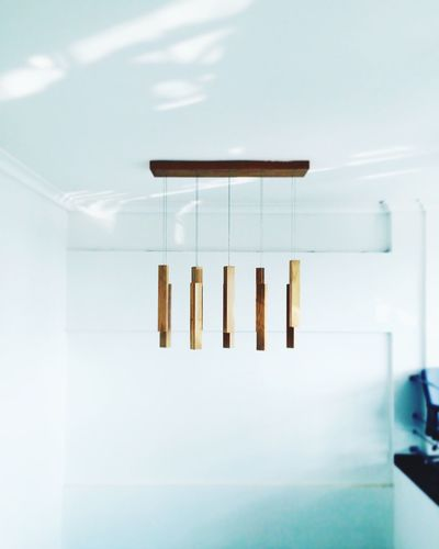 Wooden wind chime hanging on ceiling at home