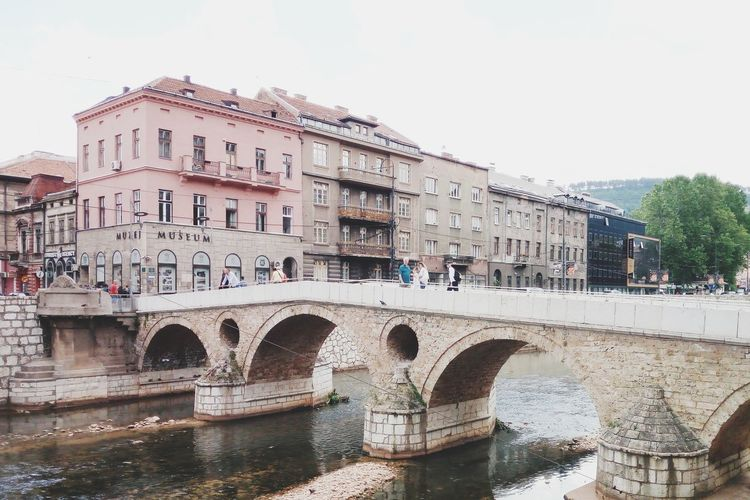Latin bridge in Sarajevo City Bridge - Man Made Structure Clear Sky Water River Arch Sky Architecture Building Exterior Built Structure Arch Bridge Historic Old Town History Building The Past Historic Building Civilization