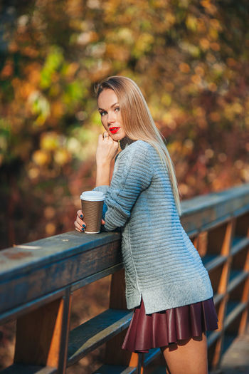 Woman looking away while sitting on railing