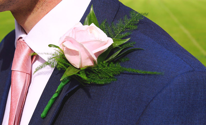 Midsection Of Man With Pink Rose Boutonniere During Wedding