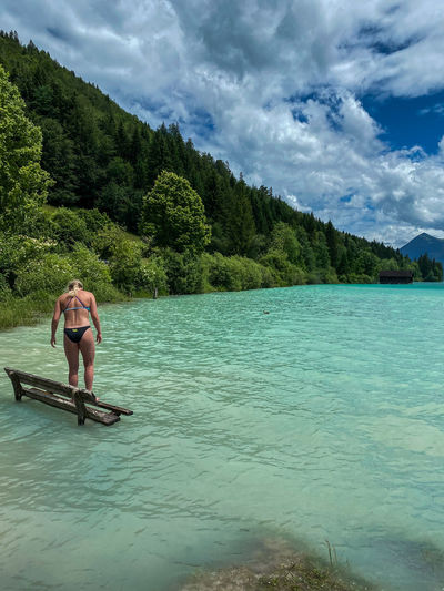 Young lady on a bench in alpine lake walchensee against mountain and sky
