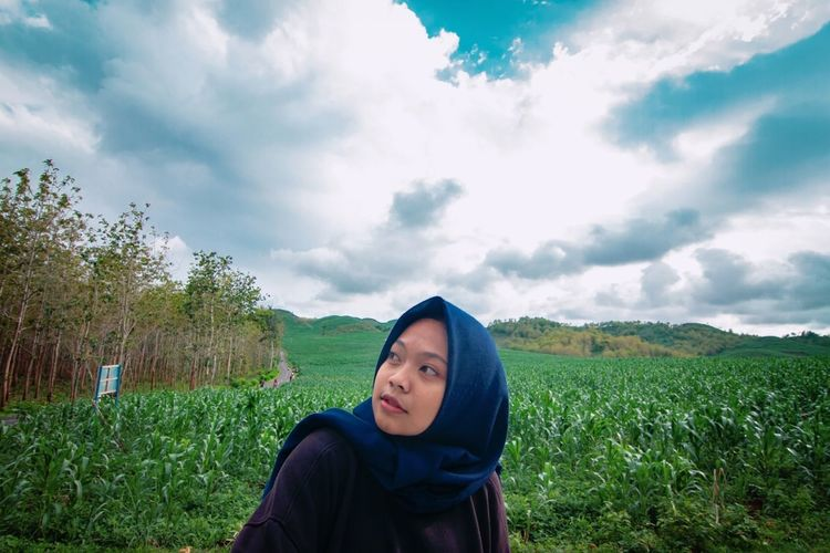 Young woman in headscarf on land against sky