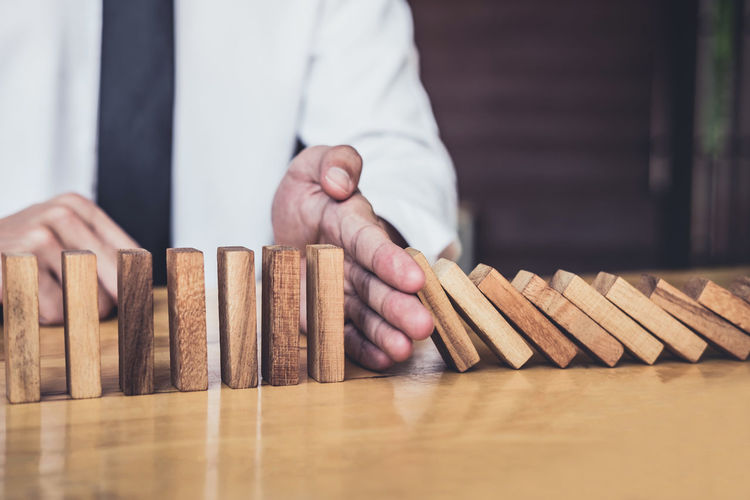 Midsection Of Businessman Playing With Toy Blocks On Table