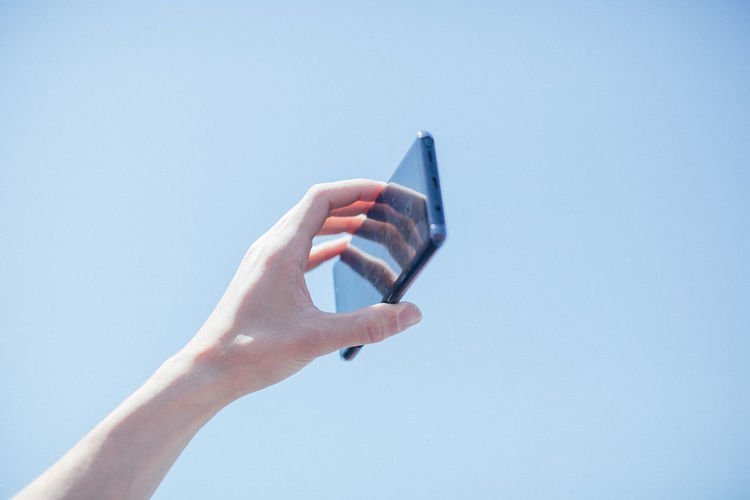 Cropped Image Of Woman Holding Mobile Phone Park
