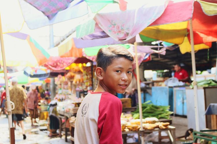 Portrait of smiling girl sitting at market stall