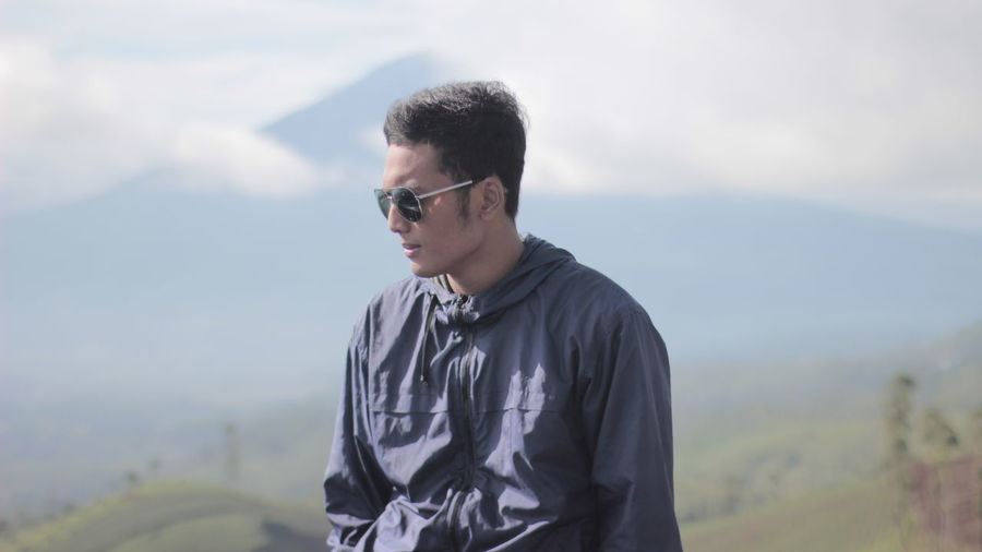 Young man wearing sunglasses while standing against mountain