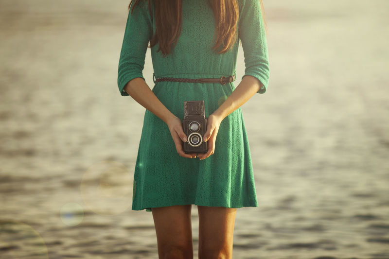 Close-Up Of Young Woman Holding Camera