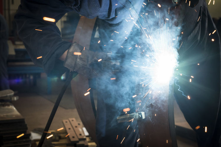Close up on worker welding Welding Metal Metal Industry Occupation Sparks Heat - Temperature Safety Welder Industrial Worker Factory Light Industry Smoke Laboratory Job Manufacture Manufacturing Equipment Fire Laborer Welded Fabricate Workplace Making Assembly