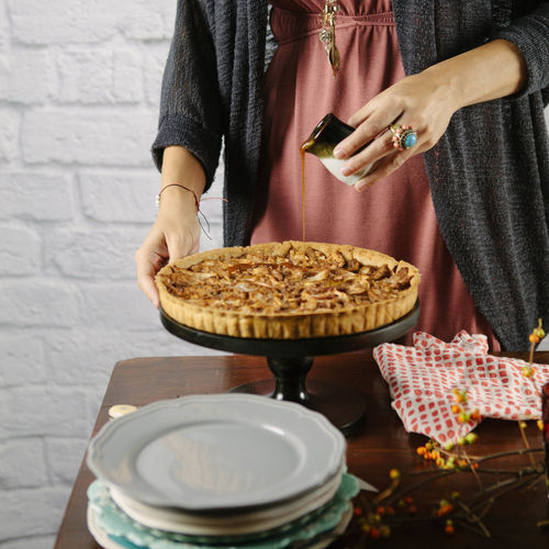 Woman pours caramel sauce on an apple tart for serving Adult Dessert Food Food And Drink Holding One Person Ready-to-eat Serving Food And Drinks Sweet Food Tart - Dessert