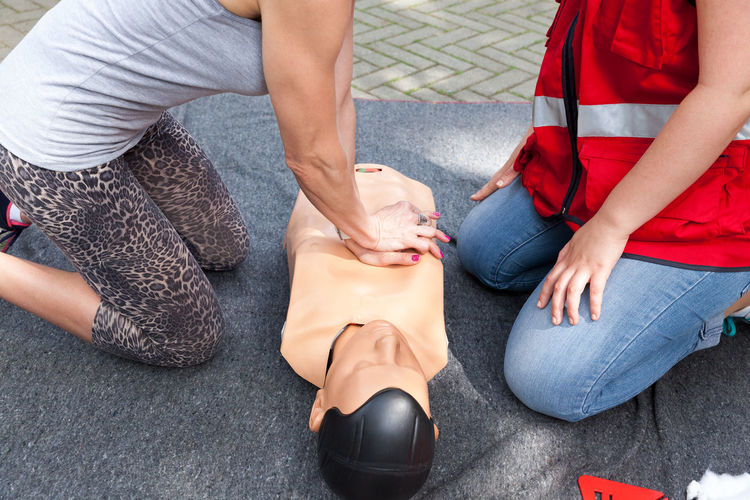 Midsection of paramedics performing cpr on dummy