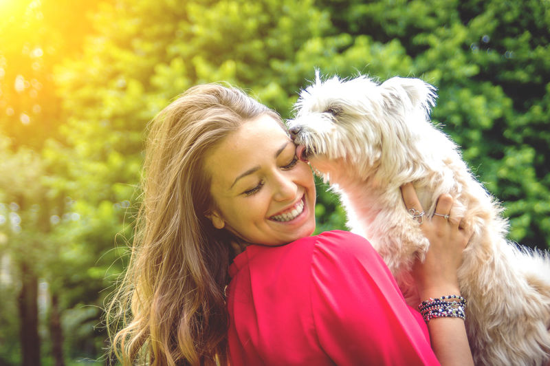 Close-up of dog licking happy woman face against trees in park