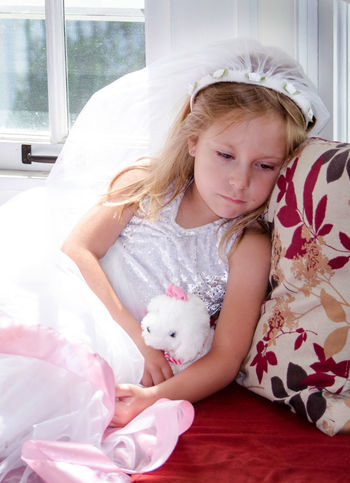 a tired little girl plays dress up but has to take a moment to rest with her favorite stuffed toy Females Kids Casual Clothing Child Childhood Costume Cute Dress Up Females Front View Furniture Girl Girls Hair Home Interior Indoors  Innocence Leisure Activity Lifestyles One Person person Real People Rest Sad Tire