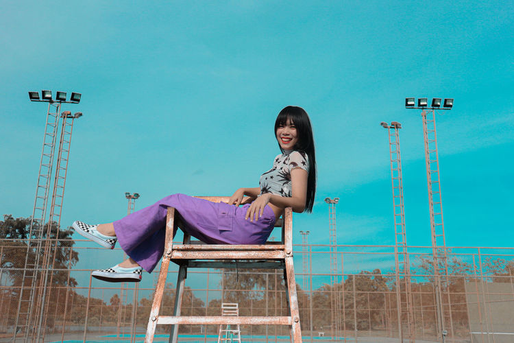Low angle portrait of woman sitting on chair against clear blue sky
