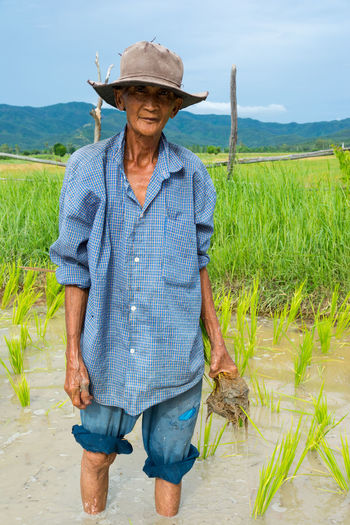 Chiang Mai, Thailand - Jun 30, 2016 Old farmer planting rice in rice field near Chiang Mai, Thailand Blue Casual Clothing Chiang Mai | Thailand Day Field Focus On Foreground Front View Grass Green Color Hat Labor Landscape Leisure Activity Lifestyles Mature Adult Old Outdoors Person Plant Planting Sky Smiling Standing Three Quarter Length Young Adult