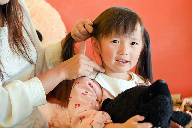 Mother combing daughter hair at home