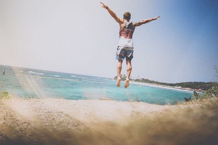 Rear view of man jumping with arms outstretched at beach against sky