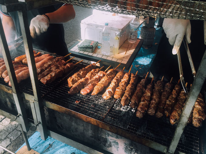 Cropped Image Of Men Grilling Skewers At Market Stall