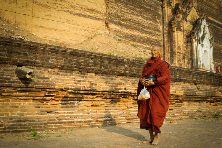 A Buddhist monk go back to the Mingun Pagoda after the daily morning walk to receive food in Mandalay, Myanmar Mandalay Myanmar Cultures Culture Morning Color Religion Buddha Buddhism Spirituality Belief Architecture Built Structure Building One Person Clothing Real People Adult Men Monk  Walking Shadow Red Brick Temptation Pagoda Stupa Old Standing Holding Tradition Day Daylight Sunlight Light And Shadow Meditation Mindfulness