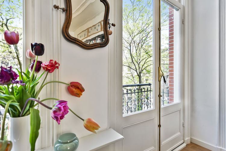Flower vase by window at home