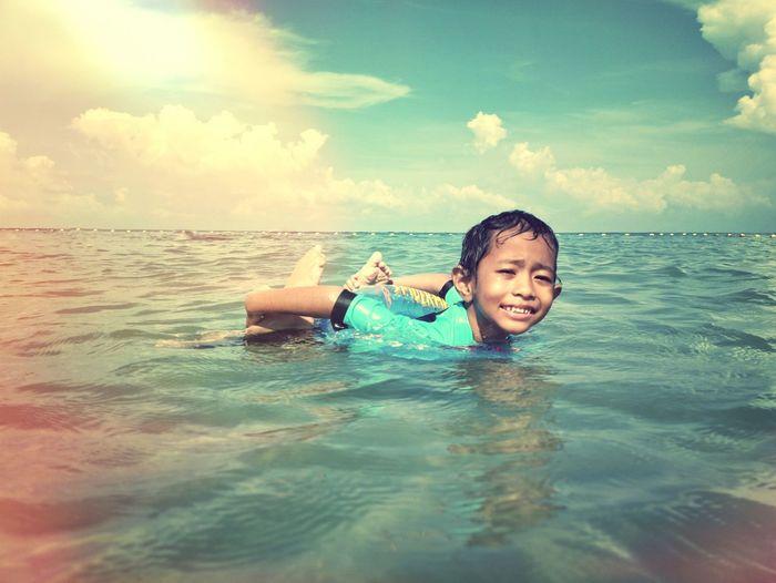 Portrait of boy swimming in sea against sky