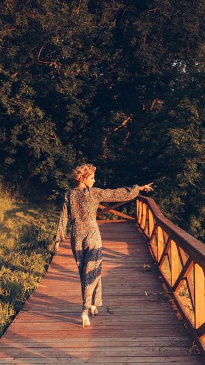 Rear view of woman walking on footbridge
