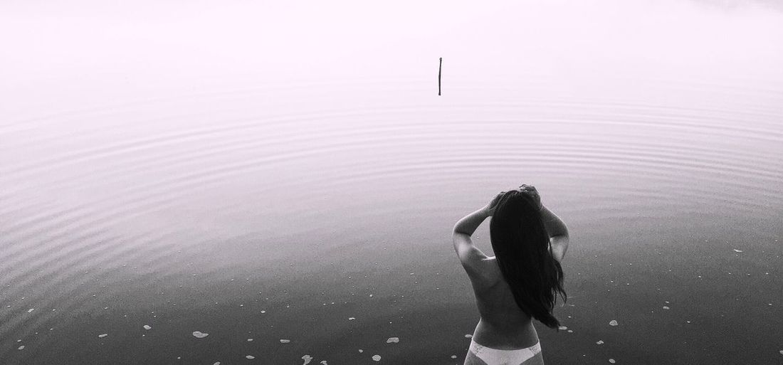 Rear view of shirtless woman standing in sea