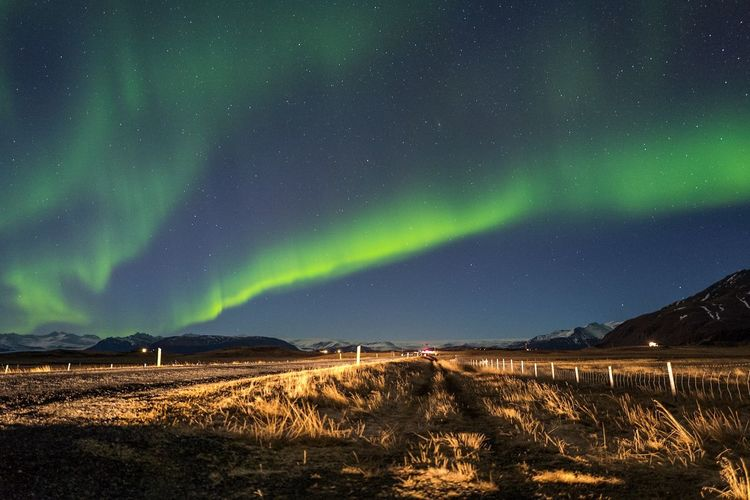Scenic View Of Field Against Sky During Aurora Borealis