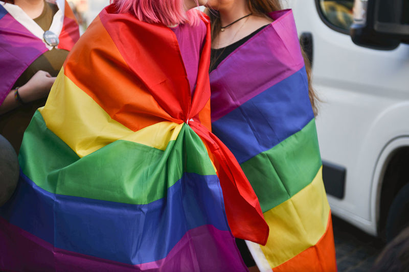 Woman Wearing Rainbow Flag During Parade In City