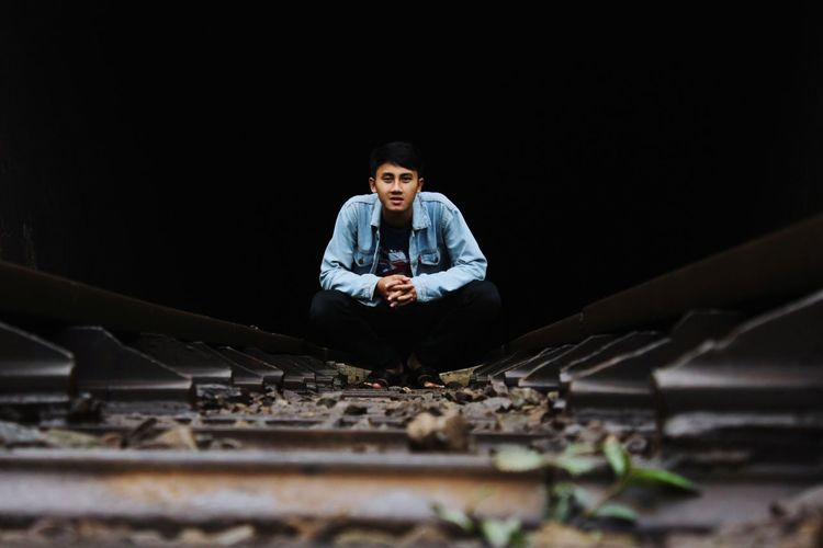 Full length portrait of young man sitting on railway track