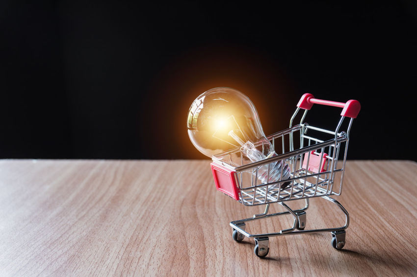Energy saving light bulb with stacks of coins and shopping cart for saving, financial and shopping concept. Shopping Cart Indoors  Consumerism No People Shopping Metal Table Retail  Technology Copy Space Still Life Basket Store Close-up Container Food And Drink Studio Shot Business Illuminated Food Groceries Wheel