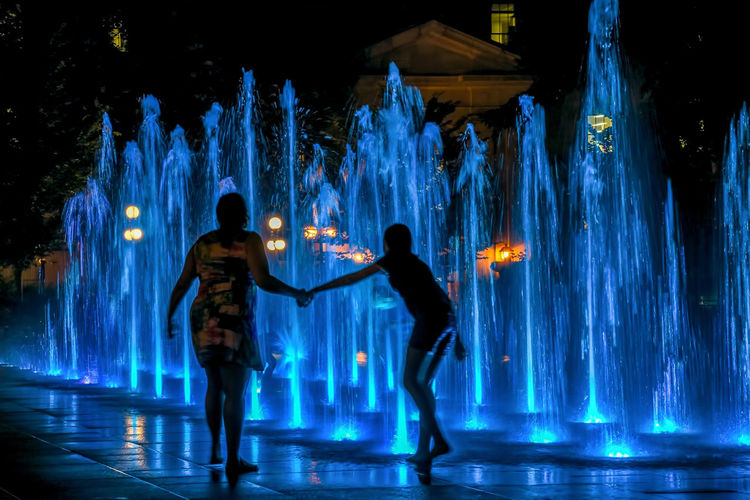 Friends standing by illuminated water at night