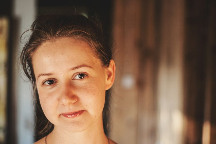 Close-up portrait of smiling young woman at home