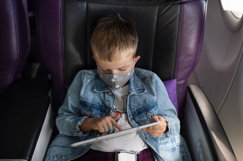 High angle view of boy wearing flu mask using digital tablet in airplane